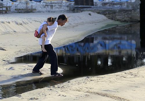 Người dân đi qua bờ biển ở Đà Nẵng bị nước thải chảy tràn qua. Ảnh: Nguyễn Đông.