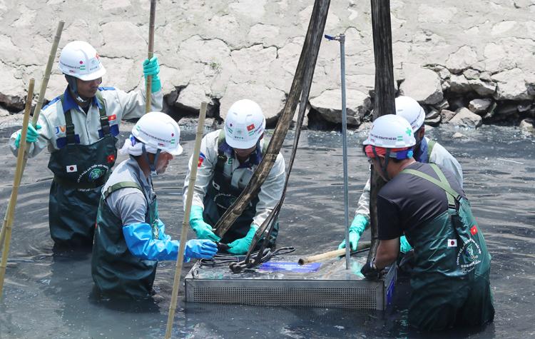 Các kỹ sư và công nhân hạ thiết bị xử lý ô nhiễm xuống sông Tô Lịch sáng 16/5. Ảnh: Võ Hải.