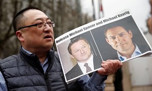Louis Huang, thành viên tổ chức Tự do và Dân chủ vì Trung Quốc có trụ sở tại Vancouver, cầm ảnh Spavor (trái) và Kovirig (phải), yêu cầu trả tự do cho hai người. Ảnh: Reuters.