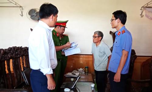 Cơ quan điều tra đọc lệnh khởi tố nghi can Trần Văn Phú (người đeo kính phía trong) - cựu Chủ tịch xã Quảng Lộc. Ảnh: Lam Sơn.
