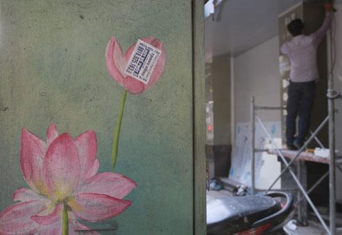 Tủ điện trang trí hoa sen hồng bị dán đè quảng cáo khoan cắt bê tông. Ảnh: Tất Định