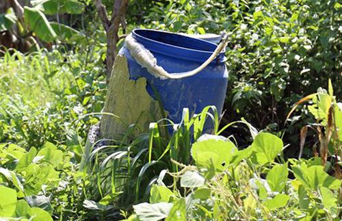 Bình nhựa mà nhóm nghi can dùng để ướp xác nạn nhânnằm trong vườn căn nhà ở xã Hưng Hòa. Ảnh: Phước Tuấn.
