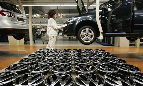 Công nhân Đức bên loạt logo gắn mui xe tại nhà máy của Volkswagen ở Wolfsburg, Đức. Ảnh: CNN