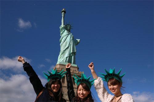 Du khách Trung Quốc chụp ảnh trước tượng Nữ thần Tự do ở New York Mỹ. Ảnh: Reuters.