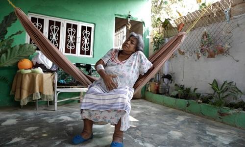 Lesbia Avila ôm bụng vì đau trong lúc chờ có điện ở nhà bà. Ảnh: Reuters.
