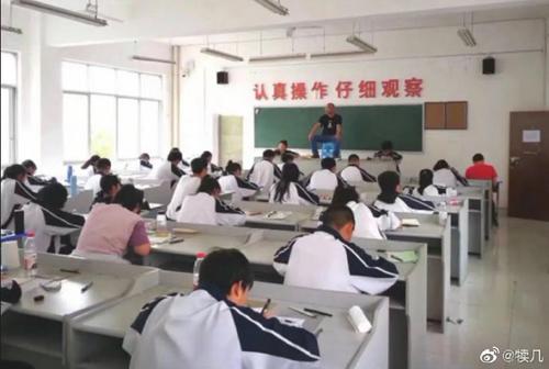 Thấy giáo bê ghế lên bàn ngồi để coi thi. Nguồn: Weibo