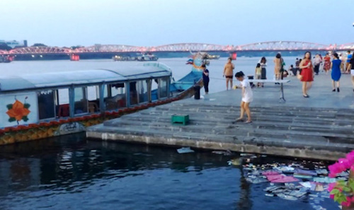 Nhiều người dân ở Huế có thói quen rải vàng mã xuống sông Hương. Ảnh: CTV