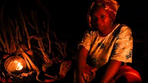 Kasia Hassan, mẹ của 9 đứa con, nấu nướng cho gia đình dưới ánh sáng tù mù của nến parafin. Ảnh: Sam Eaton.