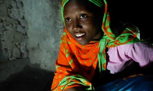 Nuru Sheha, 14 tuổi, học bài buổi tối dưới ánh đèn LED chạybằng năng lượng mặt trời tại làng Matemwe, đảo Zanzibar. Ảnh: Sam Eaton.