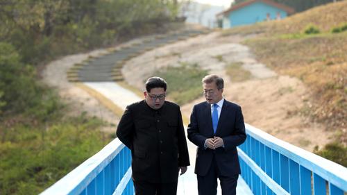 Kim Jong-un (trái) và Tổng thống Hàn Quốc Moon Jae-in đi dạo trên cầu gỗ tháng 4/2018. Ảnh: AFP.