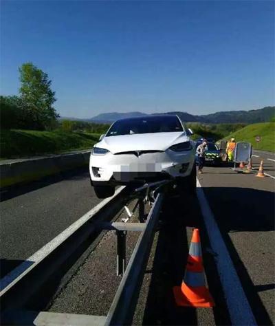 Mẫu ôtô chạy điện nằm thăng bằng trên dải phân cách. Ảnh: Facebook