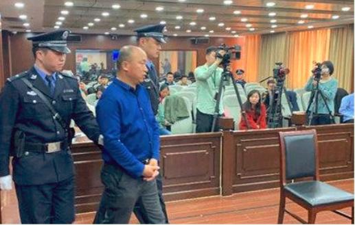 Quách Cường (áo xanh tối) bị dẫn giải ra trước tòa.