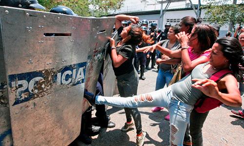 Người nhà tù nhân đụng đột với cảnh sát tại thành phố Valenciasau khi hỏa hoạn xảy ra khiến 68 người chết hồi tháng 3/2018. Ảnh: CNN.