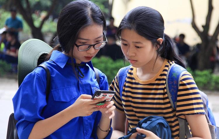 Tình nguyện viên Đại học Sư phạm Hà Nội hỗ trợ thí sinh tìm địa điểm thi. Ảnh: Dương Tâm