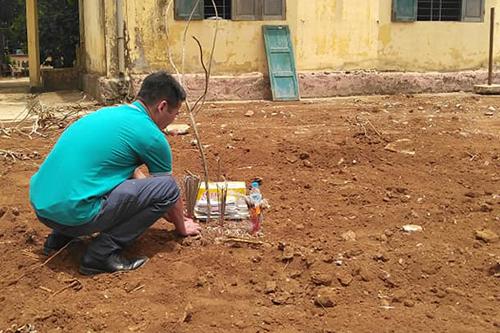 Người thân liệt sĩ Lưu Văn Phóng thắp hương ở địa điểm gốc cây xà cừ, nơi phát hiện hài cốt. Ảnh: Quốc Khánh