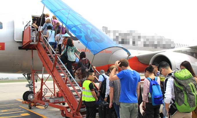 Hành khách lên máy bay tại sân bay Nội Bài.