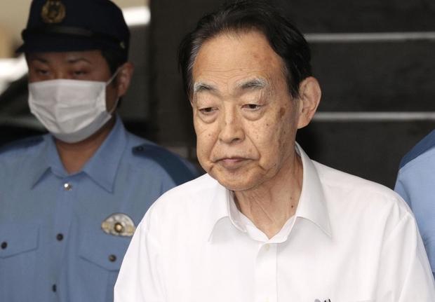 Nghi phạm Hideaki Kumazawa (áo trắng) bị cảnh sát áp giải.