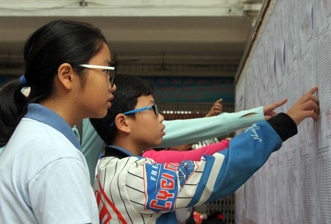 Thí sinh dự khảo sát vào lớp 6 trường THPT Trần Đại Nghĩa xem danh sách phòng thi. Ảnh: Mạnh Tùng