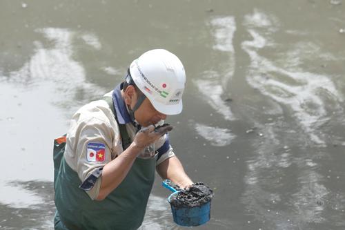 Chuyên gia Nhật Bản kiểm tra mẫu bùn khu vực thí điểm ngày 6/6. Ảnh: Tất Định