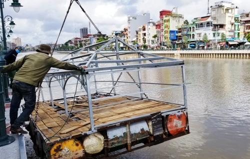Nhà chức trách quận Hồng Bàng cẩu ngôi nhà thứ 3 trên sông Tam Bạc lên bờ để sửa chữa lại cho phù hợp. Ảnh: Giang Chinh