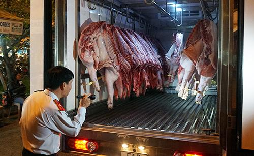: Kiểm tra biểu hiện trên thịt heo trước khi nhập vào chợ đầu mối Hóc Môn. Ảnh: Minh Tân.