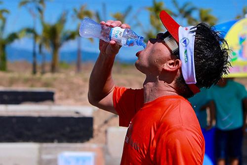 Vận động viên tham gia VnExpress Marathon bù nước khi chạy dưới nắng nóng ở Quy Nhơn (Bình Định). Ảnh: PV