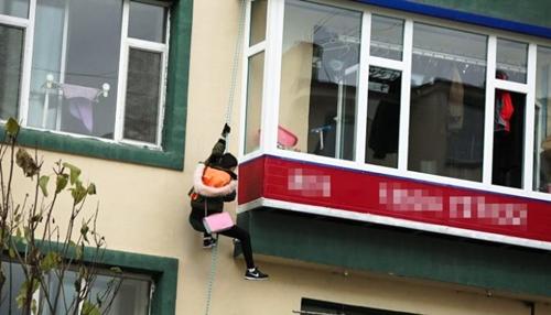 Lee Yumi trèo dây thừng từ căn hộ tầng 4 một tòa nhà ở Diên Cát, nơi cô bị nhốt suốt 5 năm. Ảnh: CNN.