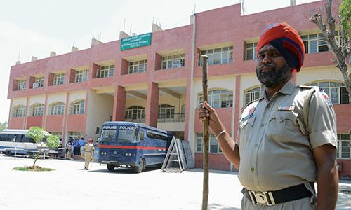 Cảnh sát đứng gác khi xe buýt chở các nghi phạm đến tòa án ởPathankot, bang Jammu và Kashmir, Ấn Độ hôm nay. Ảnh: AFP