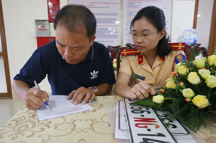 Một tài xế làm thủ tục cấp đổi biển số, sang tên ở Cục CSGT khi mua bán xe cho cơ quan . Ảnh: Bá Đô
