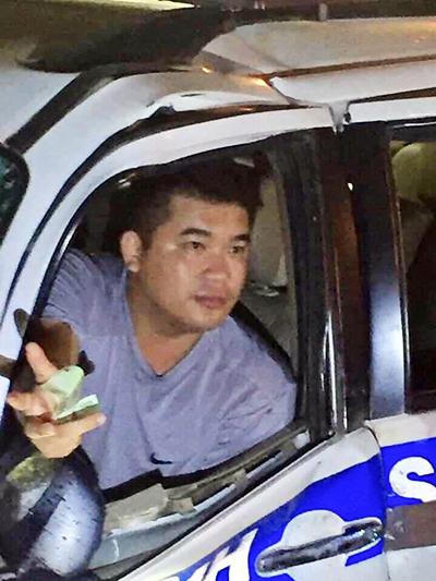 Trung úy Phan Hoàng Ân rút tiền đưa người dânsau khi gây tai nạn.