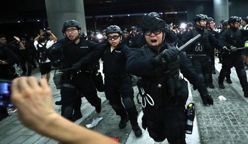 Cảnh sát Hong Kong dùng dùi cui đẩy lui người biểu tình trong cuộc đụng độ rạng sáng 10/6. Ảnh: SCMP.