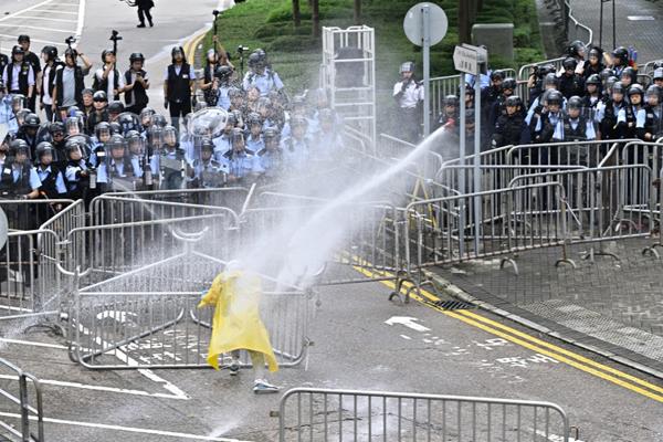 Cảnh sát phun vòi rồng vào một người biểu tình gần trụ sở chính quyền. Ảnh: AFP.