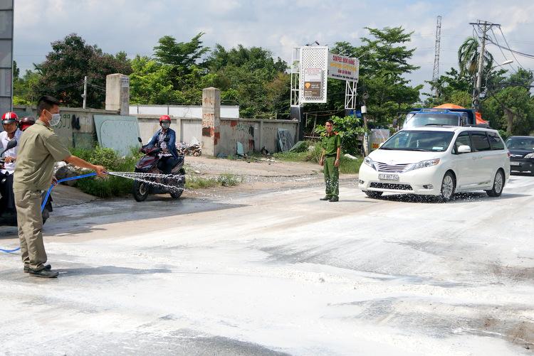 Vôi bột được rải trắng đường ở chốt kiểm dịch trên đường Nguyễn Duy Trinh. Ảnh: Minh Tân.