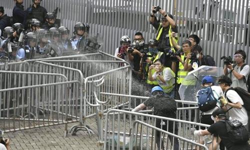Cảnh sát xịt hơi cay vào người biểu tình gần tòa nhà cơ quan lập pháp Hong Kong. Ảnh: CNN.