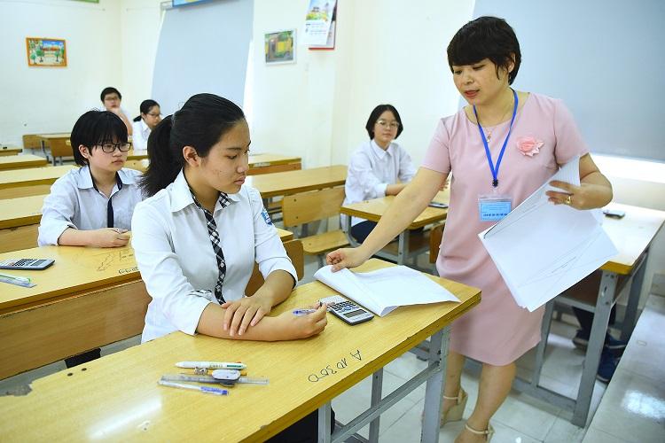 Giám thị phát giấy thi cho học sinh trong buổi thi vào lớp 10 hôm 1/6 tại Hà Nội. Ảnh: Giang Huy