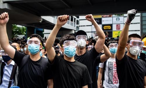 Người biểu tìnhđeo kính bảo hộ và khẩu trang tại bên ngoài trụ sởHội đồng Lập pháp Hong Kong ngày 12/6. Ảnh: AFP.