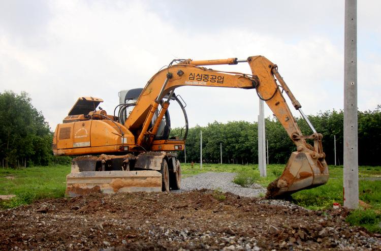 Xe múc được phường Hắc Dịch thuê tới múc con đường được mở trong dự án phân lô bán nền trái phép. Ảnh: Nguyễn Khoa.