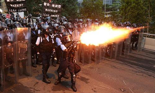 Cảnh sát phun hơi cay ngăn chặn người biểu tình xông vào trụ sở cơ quan lập pháp Hong Kong hôm 12/6. Ảnh: Reuters.