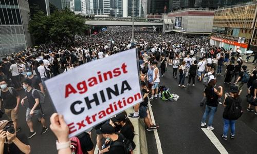 Người biểu tình giơ khẩu hiệu phản đối dẫn độ sang Trung Quốc trên đường phố Hong Kong hôm 12/6. Ảnh: AFP.