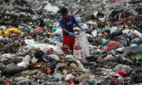 Trẻ em gom phế liệu nhựatại một bãi rác của Malaysia. Ảnh: Reuters.
