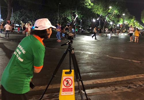Nhân viên môi trường ghi hình người xả rác ở Hồ Gươm. Ảnh: Ngọc Huyền.