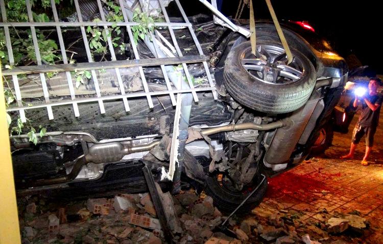 Ôtô bị nằm nghiêng, kẹt giữa bức tường nhà dân. Ảnh: Văn Trăm.