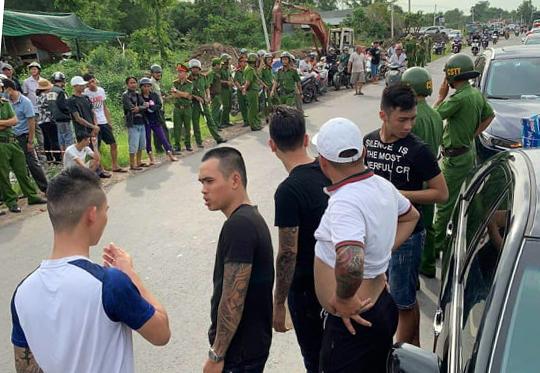 Nhóm người xăm trở đứng bao vây ôtôchở công an hôm 12/6. Ảnh: Thái Hà.