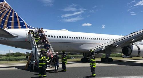 Lính cứu hỏa hỗ trợ hành khách sơ tántại sân bay quốc tế Newark Liberty ở bang New Jersey chiều 15/6. Ảnh: Twitter.