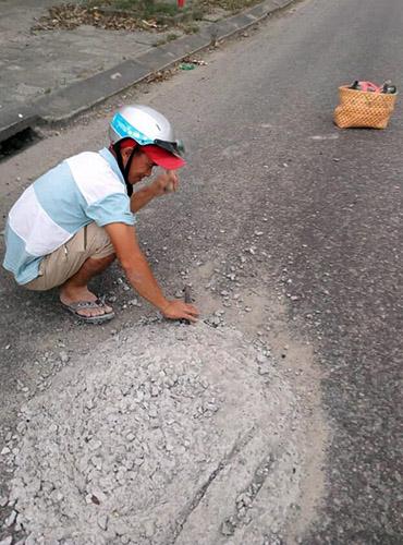 Anh Hùng đục bỏ khối bê tông trên đường. Ảnh: Doãn Văn Cảnh.