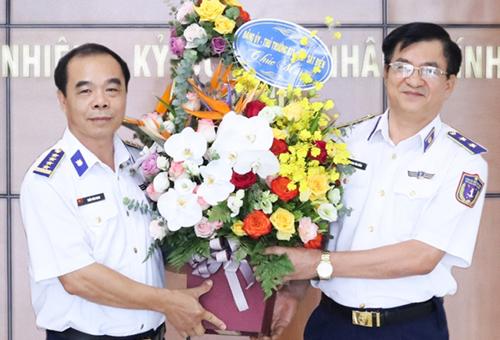 Đại tá Trần Văn Nam (trái) nhận hoa chúc mừng của Chính uỷ Cảnh sát biển.
