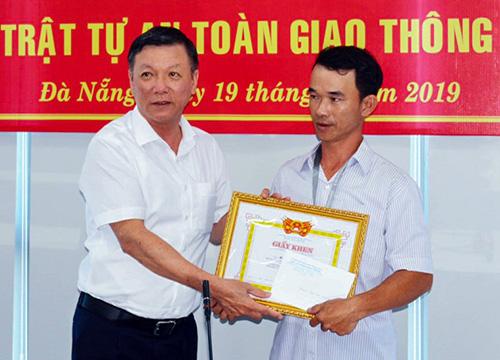 Anh Hùng (bìa phái) nhận thưởng từ lãnh đạo Ban An toàn giao thông Đà Nẵng. Ảnh: Anh Cường.