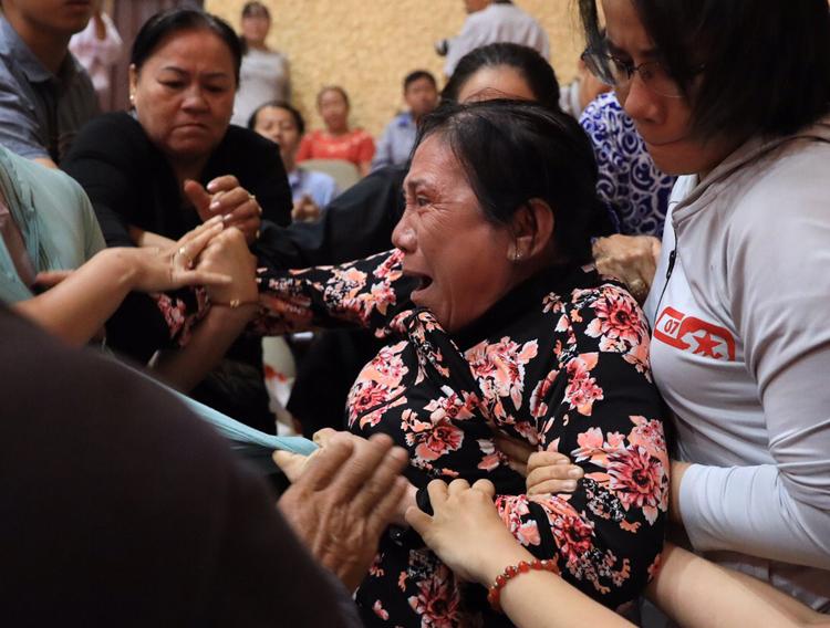 Người phụ nữ gào khóc, bị đưa ra ngoài. Ảnh: Hữu Khoa.