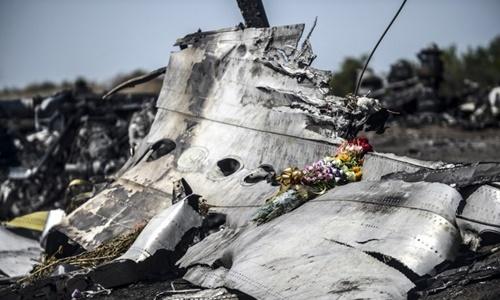 Bó hoa được người nhà nạn nhân để lại trên mảnh vỡ máy bay MH17 tại đông Ukraine tháng 7/2014. Ảnh: Reuters.