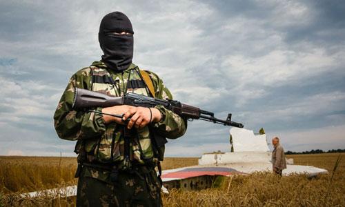 Một tay súng ly khai canh gác tại hiện trường MH17 rơi ở miền đông Ukraine năm 2014. Ảnh: Reuters.